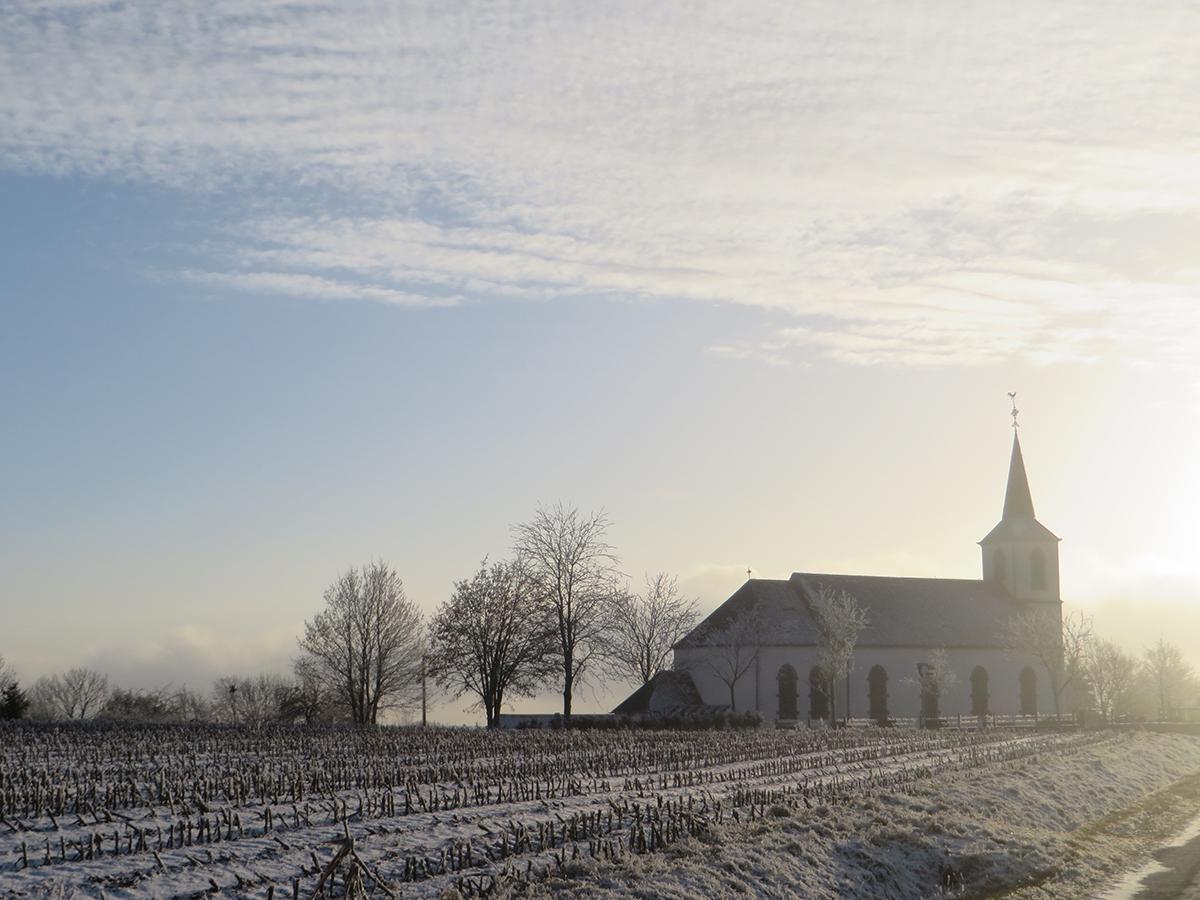 Kahler gefrorener Ackerboden im Vordergrund, hinten vor dem blassblauen Winterhimmel ein Kirche