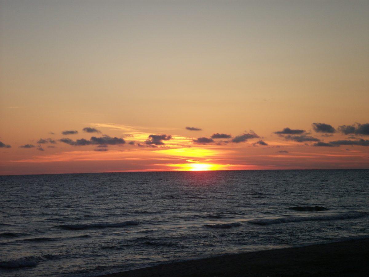 Ein Meer bei Sonnenuntergang, das Wasser vorne ist fast schwarz, darüber wie brennend die Sonne, kleine dunkle Wolken