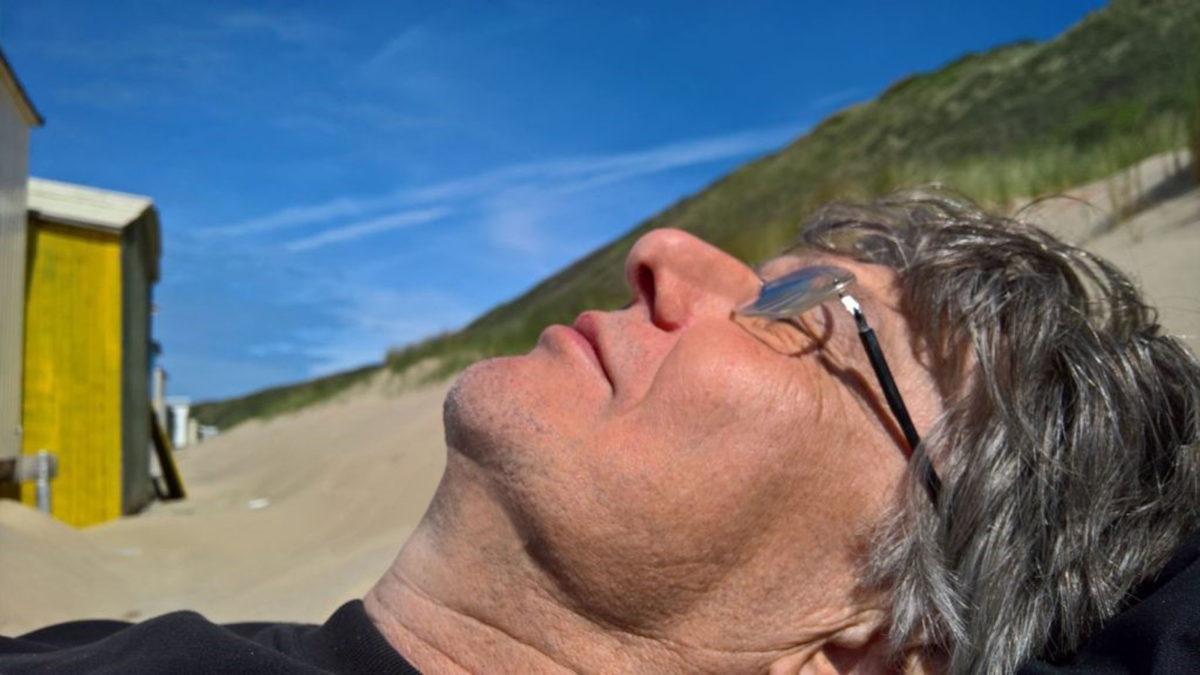 Das Gesicht des Autors, liegend en einem Sandstrand, im Hintergrund blauer Himmel, davor eine gelbe Badekabine, rechts aufsteigend eine begrünte Düne