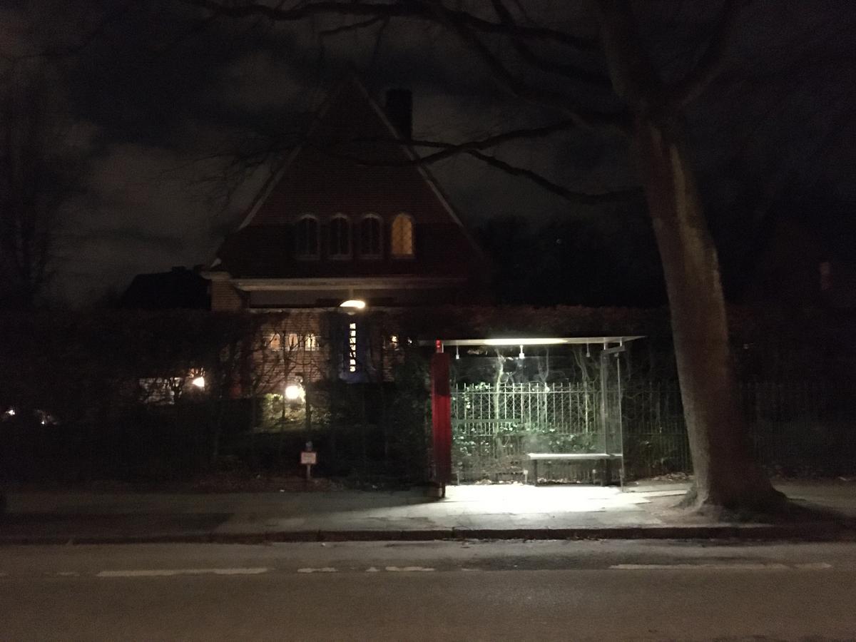 Nacht, ein Wartehäuschen an einer Bushaltestelle, erleuchtet mit fahlem Neonlicht, dahinter eine kleine Vlla im Backsteinstil mit runden Fensterbögen